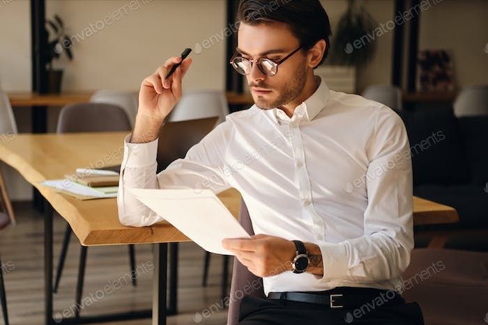 Young handsome businessman in eyeglasses thoughtfully working with papers in modern office