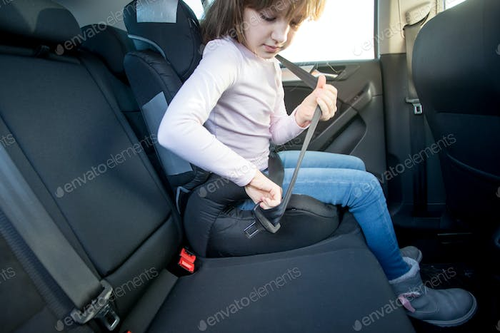 Little girl fastening belt in child car seat, security during car journey