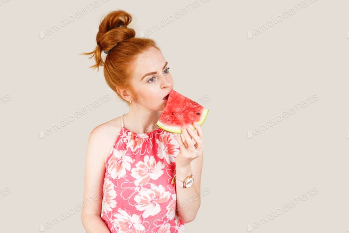 Joyful young woman holding slice of watermelon
