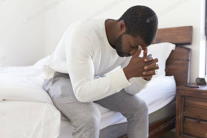 Depressed Man Looking Unhappy Sitting On Side Of Bed At Home With Head In Hands