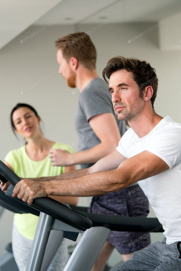 Group of people at the gym exercising on the cardio machines