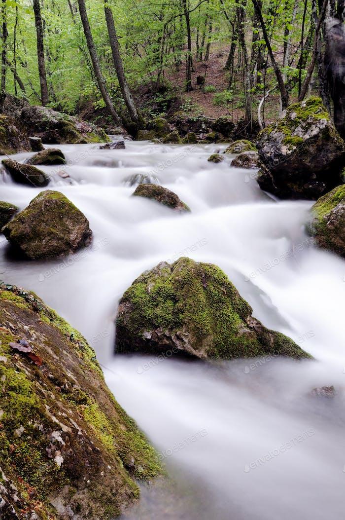 Bach mit Wasserfall und Moossteinen um