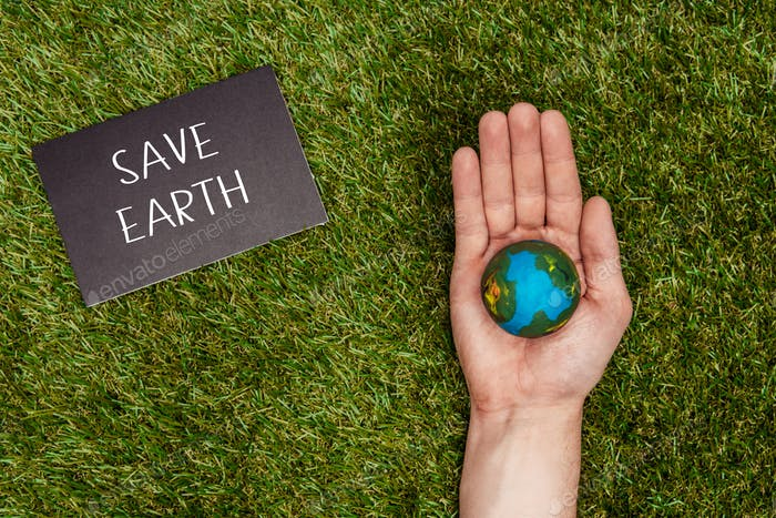 cropped image of man holding earth model in hand with sign save earth on green grass, earth day