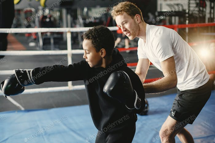 Little boy in boxing gloves on ring with trainer