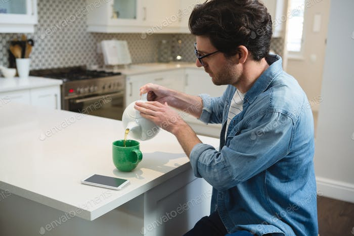 Young man pouring lemon tea into mug at home