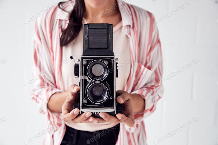 Female Photographer With Vintage Medium Format Camera On Photo Shoot Against White Studio Backdrop