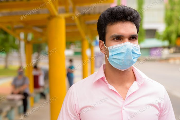 Face of young Indian businessman with mask waiting at the bus stop