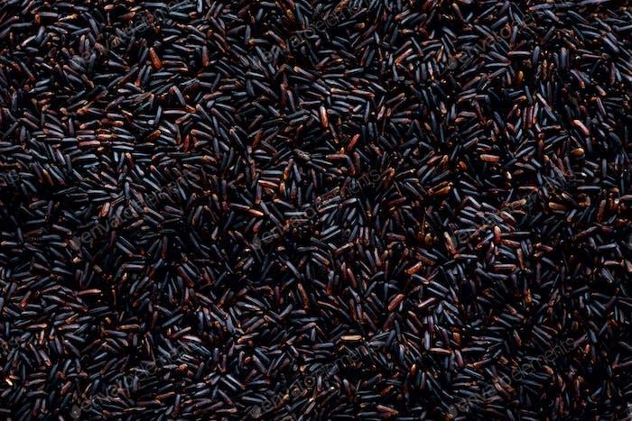 Raw dark red, balck purple rice, texture. Riceberry pattern background. Food ingredient background