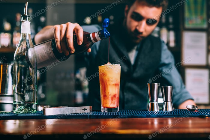 portrait of bartender pouring cherry syroup in orange summer cocktail. details of bar and restaurant