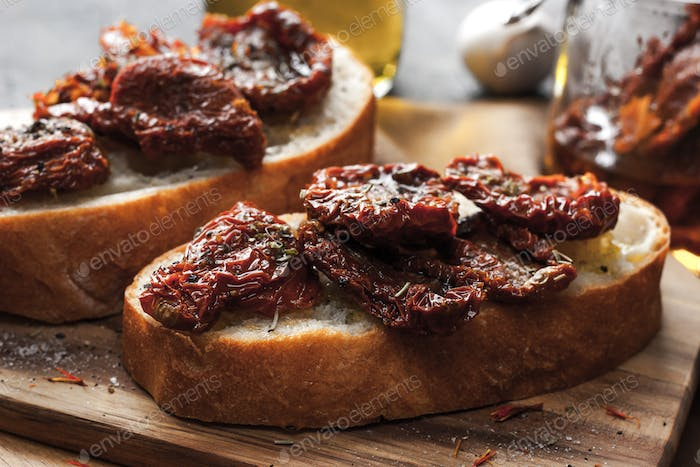 Sun-dried tomatoes on the white bread on the wooden board