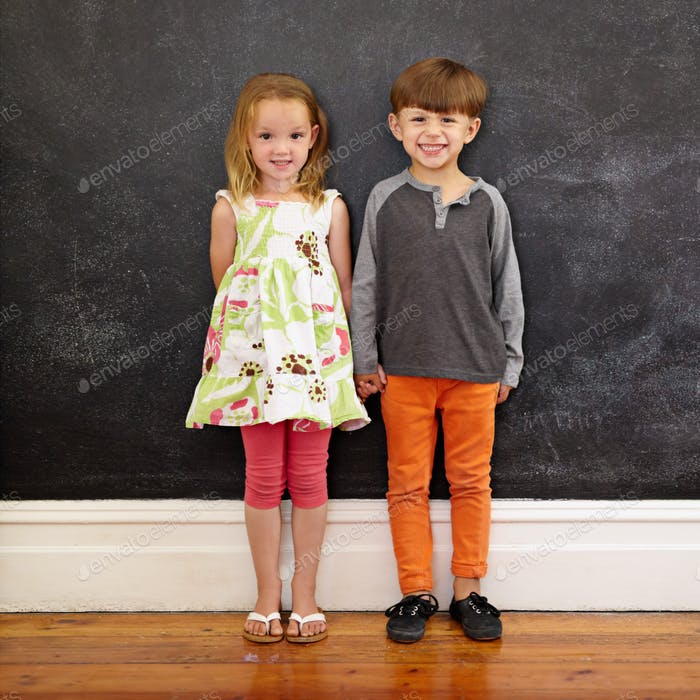 Two little kids standing together against blackboard