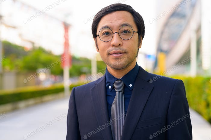Face of Asian businessman with nature in the city outdoors