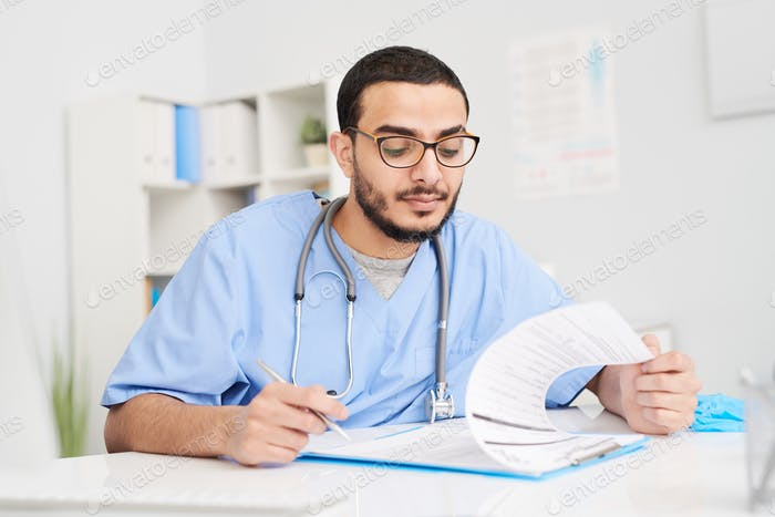Middle-Eastern Doctor Filling in Documents