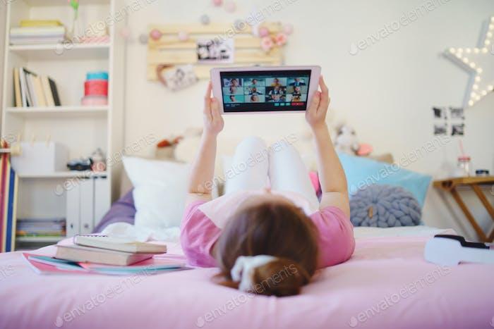 Junges Mädchen mit Tablette auf dem Bett, entspannend während der Quarantäne. Leerzeichen kopieren