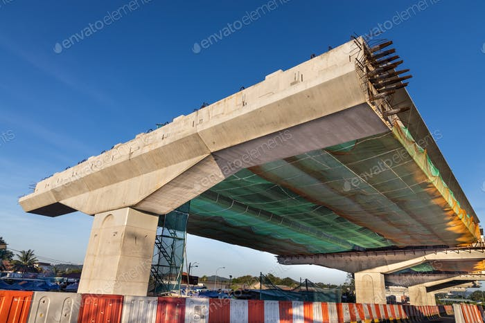Construction of highway overpass bridge infrastructure in progress with morning sun rays