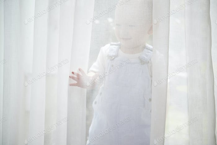Child standing behind curtain