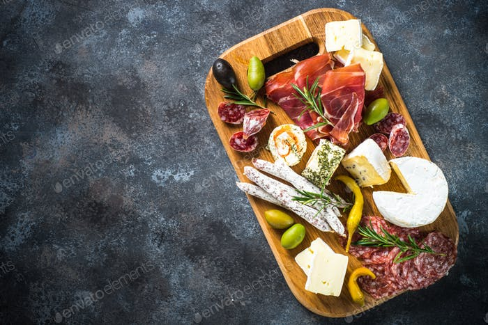 Antipasto board with sliced meat, ham, salami, cheese, olives and red wine