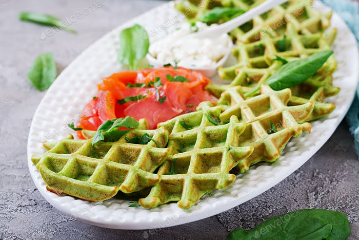Savory waffles with spinach and cream cheese, salmon in white plate. Tasty food.