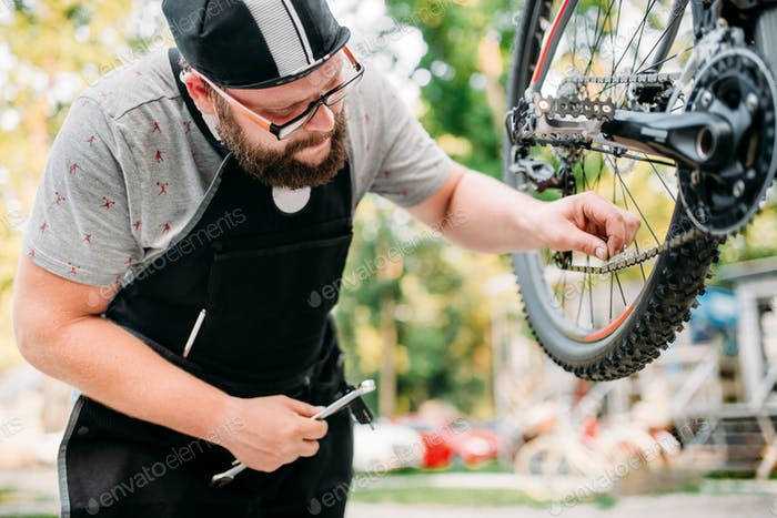 Bicycle mechanic in apron adjusts bike chain
