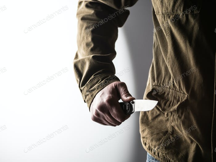 Man holding a knife in a threatening stance
