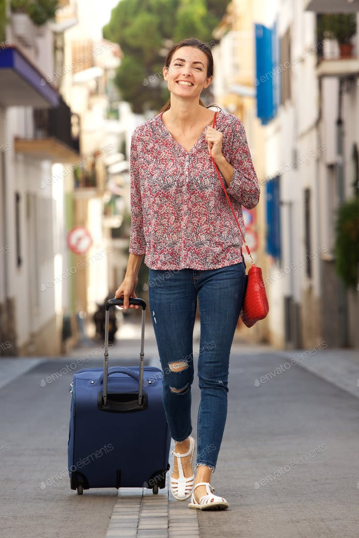 Full length attractive young woman walking on city street with luggage