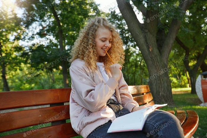 Outdoor photo of young beautiful girl blonde sits on a park bench, drinking coffee