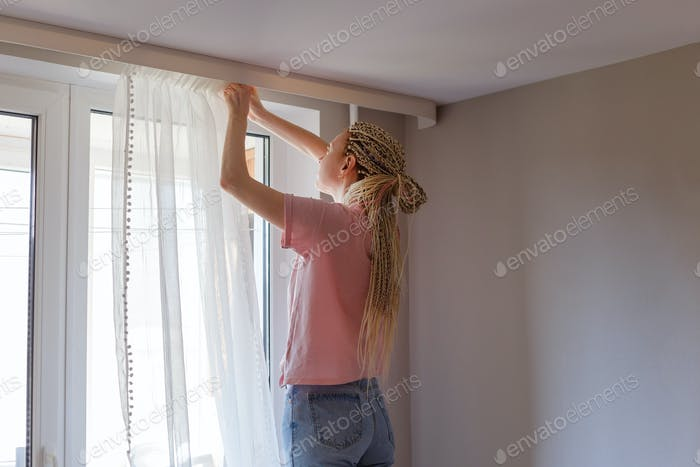 Woman hanging up curtains at the window