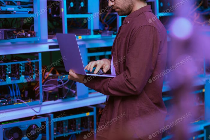 cropped shot of young computer engineer working with laptop at ethereum mining farm