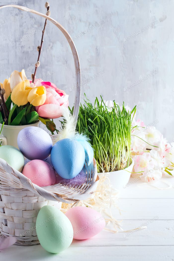 Easter basket filled with colorful hand painted Easter Eggs over a light background