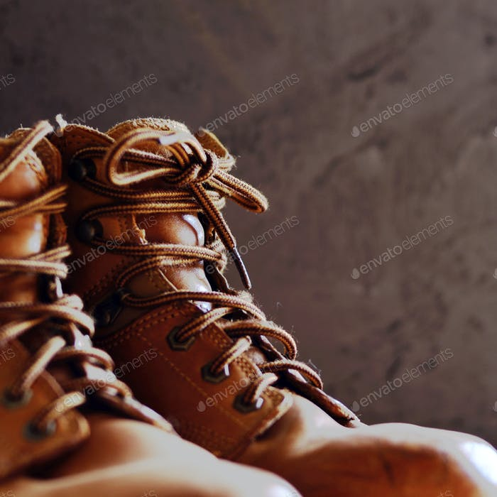 Yellow leather used work boots on concrete background closeup. P