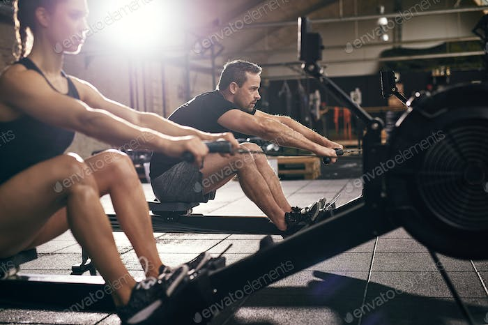 Sportsmen doing exercises with rowing machine together
