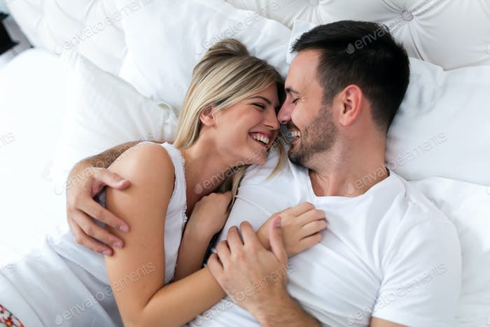 Happy couple having romantic times in bedroom
