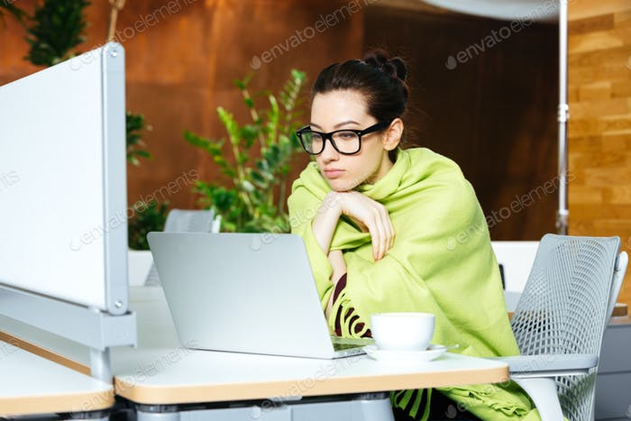 Beautiful thoughtful woman using laptop and feeling cold on workplace