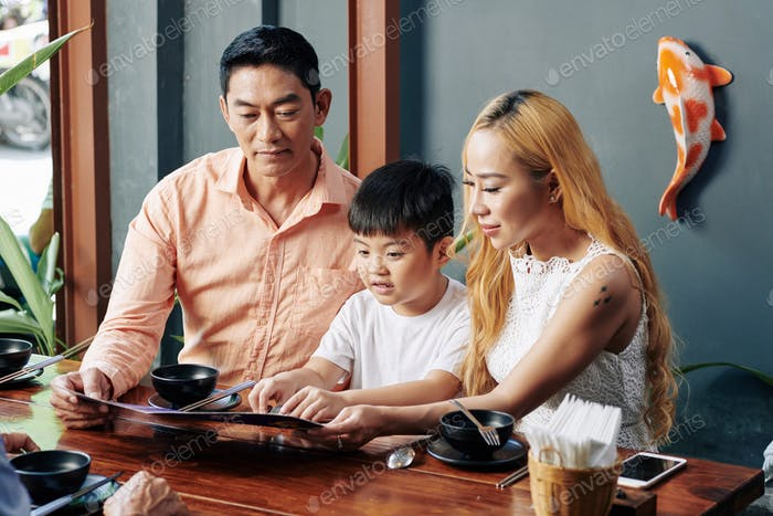 Family reading menu at cafe table