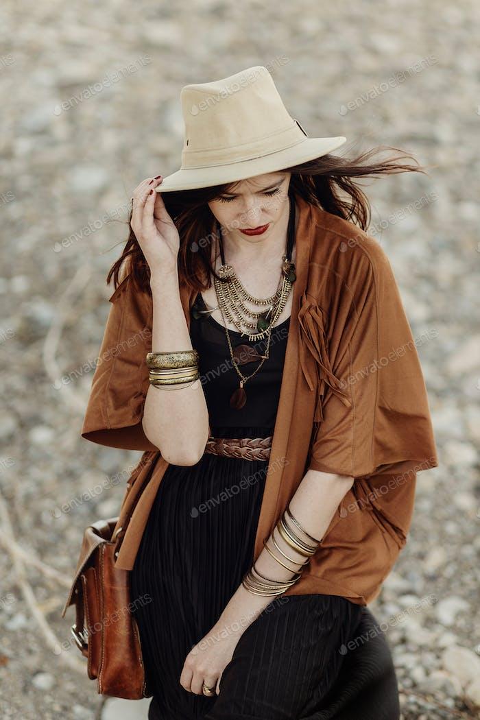 schöne stilvolle Boho Frau mit Hut, Ledertasche, Fransen Poncho und Stiefel