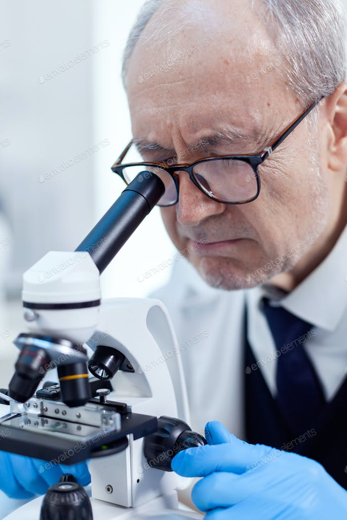 Elderly aged scientist in modern facility looking through a microscope