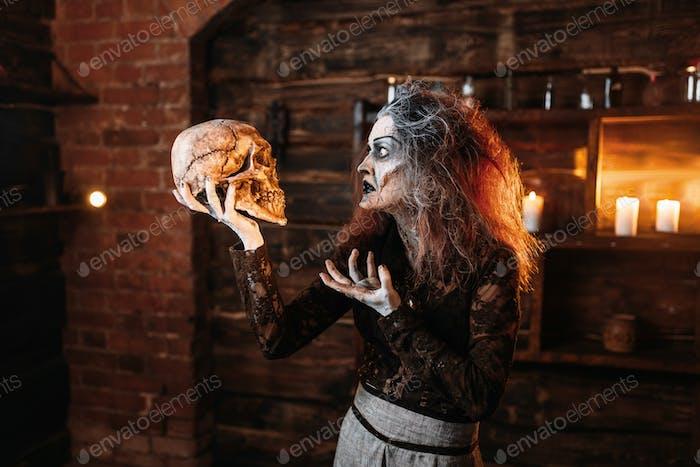 Hexe liest den Zauber, Ritual mit menschlichem Schädel