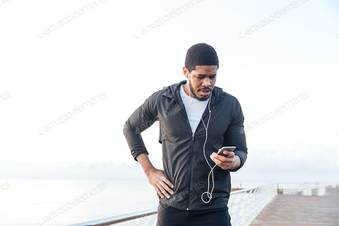 Sportsman listening to music from moble phone standing on pier
