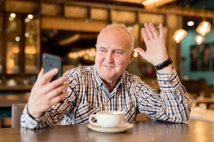 Cheerful chubby man speaking via video link in cafe