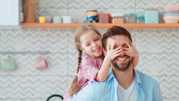 A little girl covers her dad's eyes with her hands