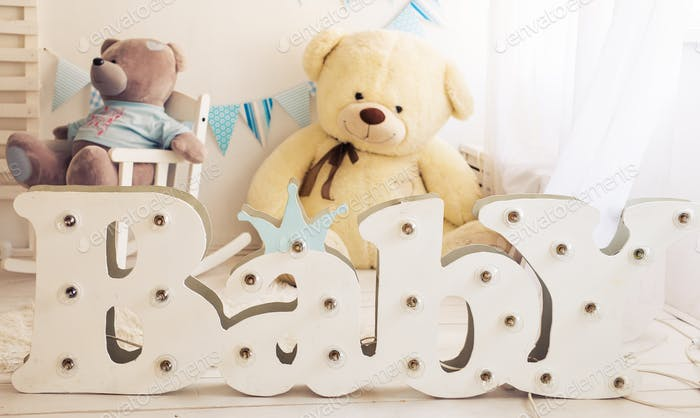 White bedroom with blue decorations designed and teddy bear ideal for both boys and girls