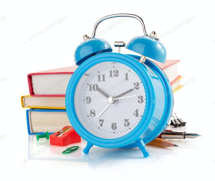 alarm clock and school supplies  on white