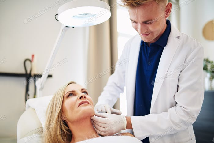 Smiling doctor performing injections on a mature client's face