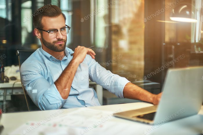 Young bearded businessman in eyeglasses and formal wear looking at laptop