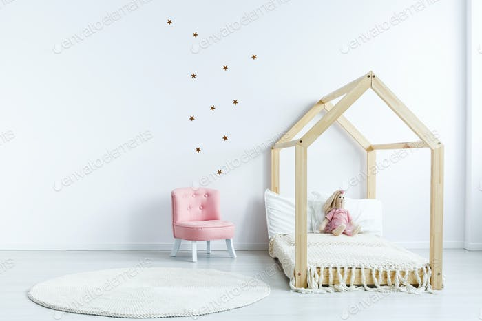 Pink chair against white wall with stickers in simple kid's bedr