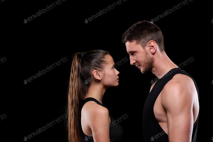 Young fit woman and man in activewear looking at one another