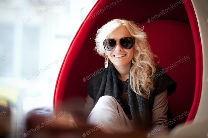 Young beautiful blond woman in big sunglasses sitting in red egg shaped armchair