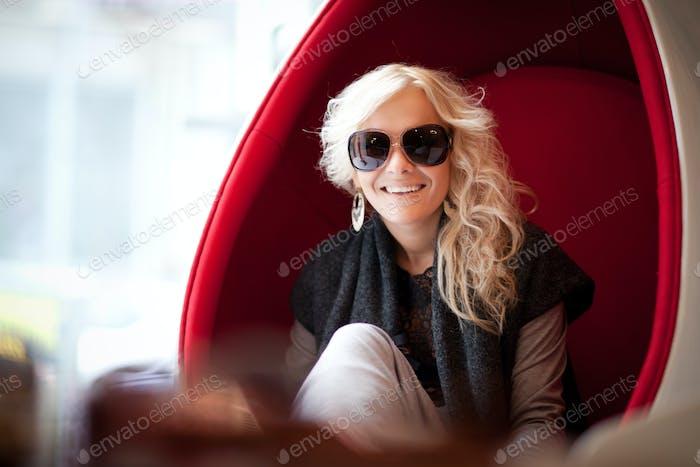 Junge schöne blonde Frau in großen Sonnenbrillen sitzen in roten Ei förmigen Sessel