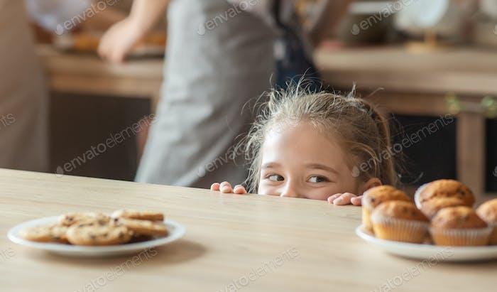 Niedlich kleines Mädchen suchen mit Freude bei Süßigkeiten