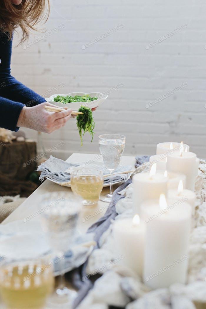 Eine Frau, die einen Teller mit Lebensmitteln auf einen Tisch legt, der mit brennenden Kerzen dekoriert ist.